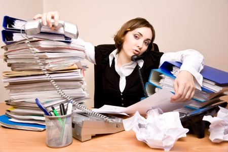 tidy: Young secretary on the phone with tons of documents Stock Photo