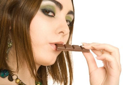 Sexy woman with a piece of choc in her lips photo