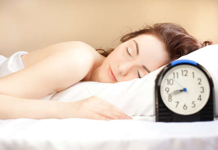 Woman sleeping in bed and alarm-clock  (focus on woman) photo