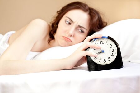 Angry woman lying a bed and holding an alarm (focus on alarm) photo