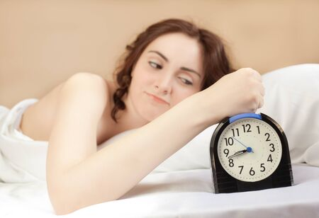 Angry woman lying a bed and press an alarm (focus on alarm) photo