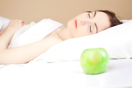 Beautiful woman sleeping in bed and green apple (focus on woman) Stock Photo