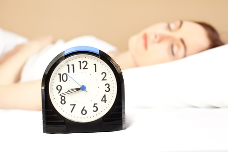 Woman sleeping in bed and alarm-clock  (focus on alarm clock) photo