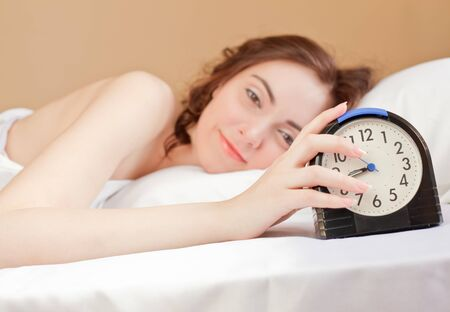 Woman lying a bed and holding an alarm photo