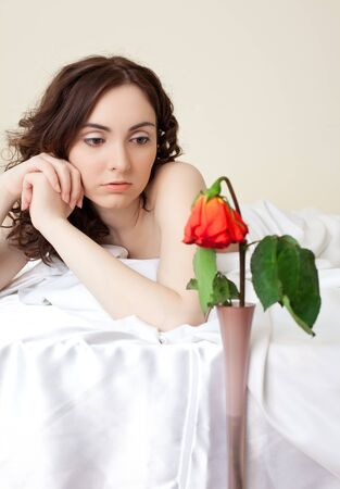 Beautiful woman in bed looking on the rose photo