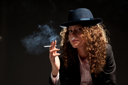 Beautiful woman standing and smoking on the black background photo