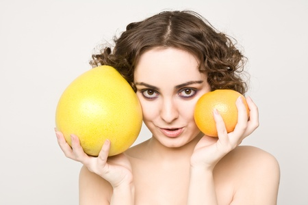 Beautiful curly girl holding grapefruit and pomelo photo