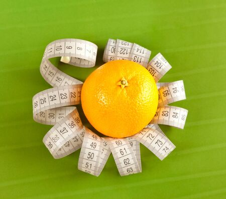 Picture of orange and measure tape on the green background photo