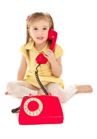 Little girl with old red phone sitting on the floor photo