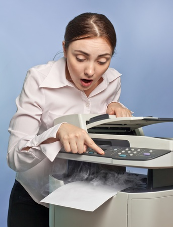 Picture of surprised businesswoman with smoking copier photo