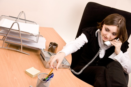 Businesswoman calling by phone at office photo