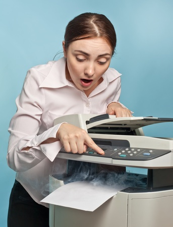 faxing: Picture of surprised businesswoman with smoking copier