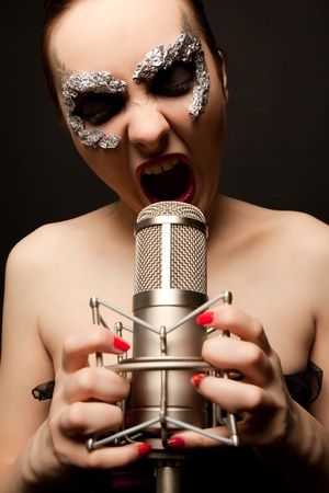 Young gothic singer standing with microphone and screaming8 photo