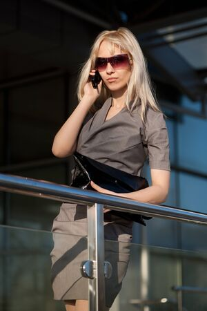 Beautiful woman in sunglasses with cellphone standing near shop photo