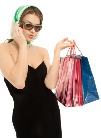 Beautiful woman with shopping bags calling by phone isolated on white photo