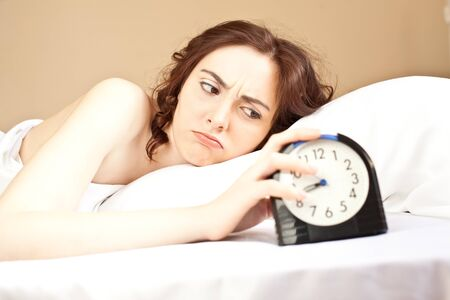 Angry woman lying a bed and holding an alarm (focus on woman) photo
