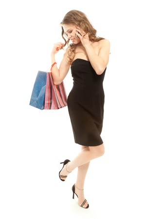 Woman with shopping bags calling by phone isolated on white photo