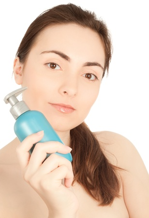 Picture of a beautiful woman with a bottle of a cream smiling photo