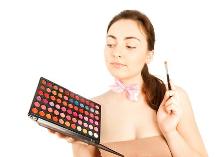 make up artist: Beautiful make up artist in pink bow-tie looking to the pallette