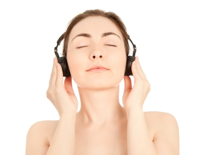 Beautiful nude woman with headphones enjoying to music photo