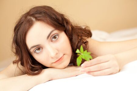 Beautiful woman holding a plant and lying in bed (focus on woman photo