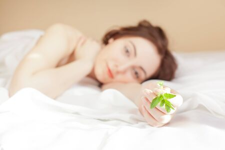 Beautiful woman holding a plant and lying in bed (focus on sprout) photo