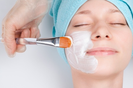 skin care: Young woman at spa procedures applying mask Stock Photo