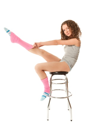 Beautiful curly haired woman sitting on the bar chair isolated on white