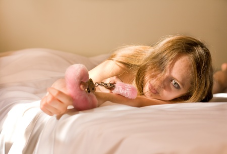 Beautiful nude woman lying in bed with handcuffs Stock Photo - 12362031