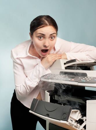 Picture of screaming businesswoman with smoking copier photo