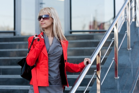 Beautiful woman in red jacket standing on the shop and looking up photo