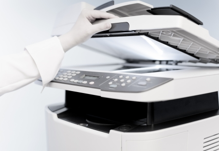 mfp: Womans hand with working copier (focus on finger) Stock Photo