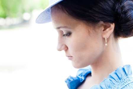Beautiful woman in blue hat looking down outdoors photo