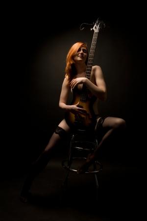 mujeres negras desnudas: Hermosa mujer sacudi� con la sentada en la silla de guitarra Foto de archivo