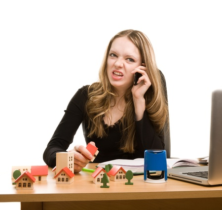 Young businesswoman writing in notebook and calling to phone photo