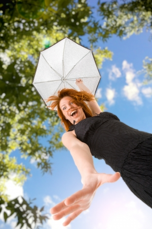 Happy red haired woman in black dress with umbrella outdoors photo