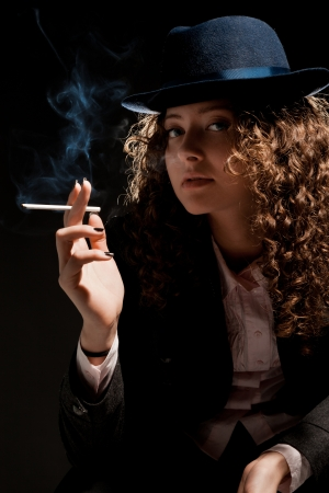 Beautiful woman standing and smoking on the black background Stock Photo - 16234636