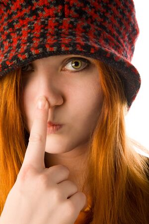 Red haired girl in knit hat touching her nose photo