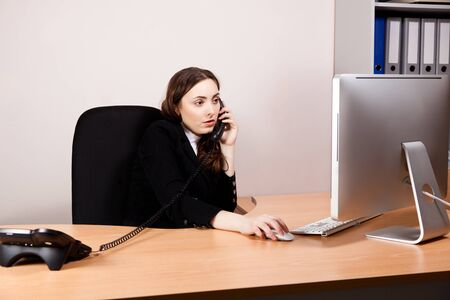 Business woman working on her computer  and calling by phone at office Stock Photo - 16578601