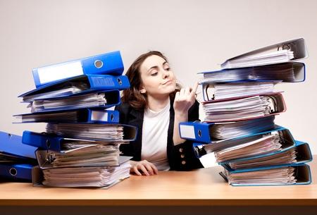 Frustrierte Geschäftsfrau mit Stapel von Ordnern im Büro