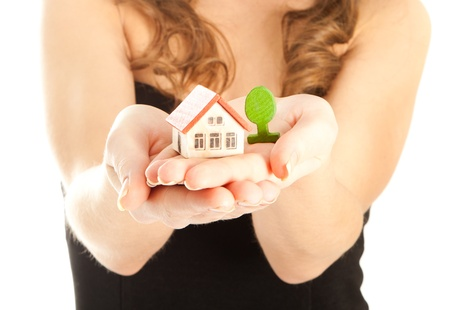 Woman s hands holding a house and a thee Stock Photo - 16635481