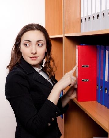 Beautiful woman taking a red folder from shelf Stock Photo - 16635726