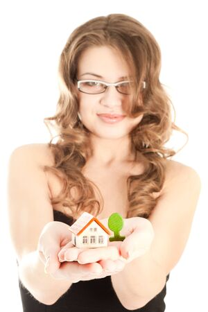 Woman holding a house with a tree in hands (focus on hands) Stock Photo - 16753693