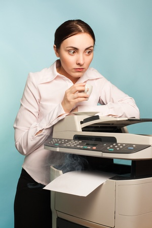 Scared secretary with coffee and smoking copier photo