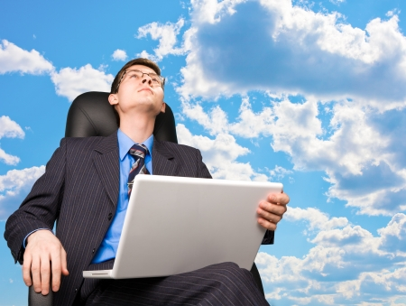 Office worker sitting in office chair at sky background Stock Photo