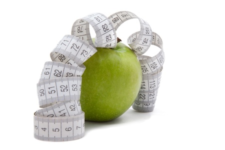 Green apple with tape measure isolated on white photo