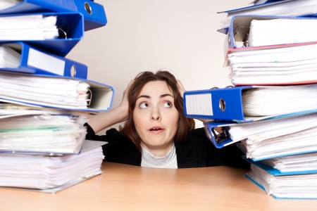 Frustrated businesswoman with stack of folders at office photo