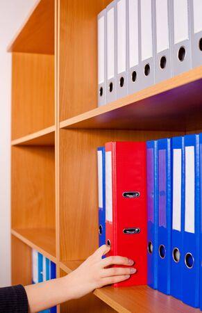 dossier: Woman s hand taking a red folder from shelf