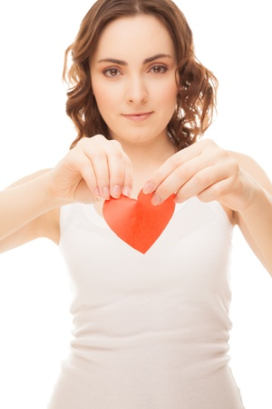 Attractive brunette young girl holding broken paper red valentine heart  focus on heart  photo