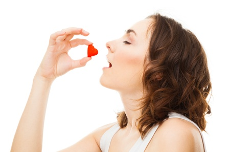 Young woman eatting candy heart isolated on white Stock Photo - 16881086
